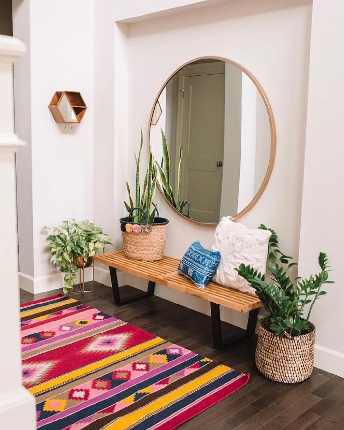 miroir rond cache pot paille pompons plantes vertes style boho éclectique tapis multicolore aménager une entrée avec banquette en bois