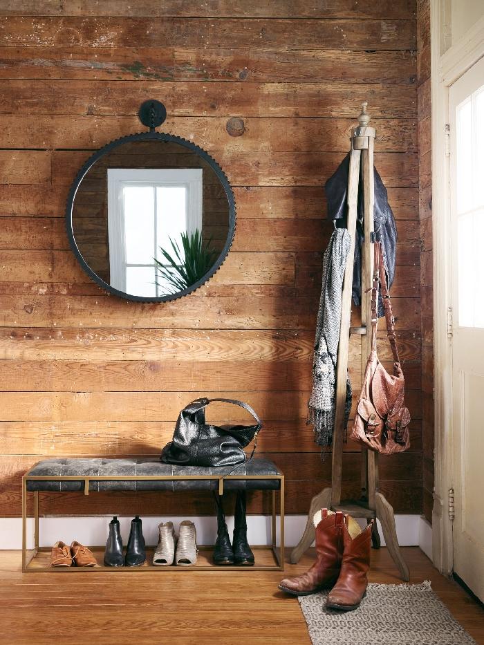 miroir rond cadre métal noirci banquette or et velours gris anthracite déco entrée maison style rustique revêtement mural bois foncé