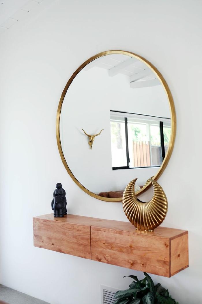 miroir rond cadre or decoration couloir moderne murs blancs meuble bois rangement accessoires décoratifs objets statuette plante verte
