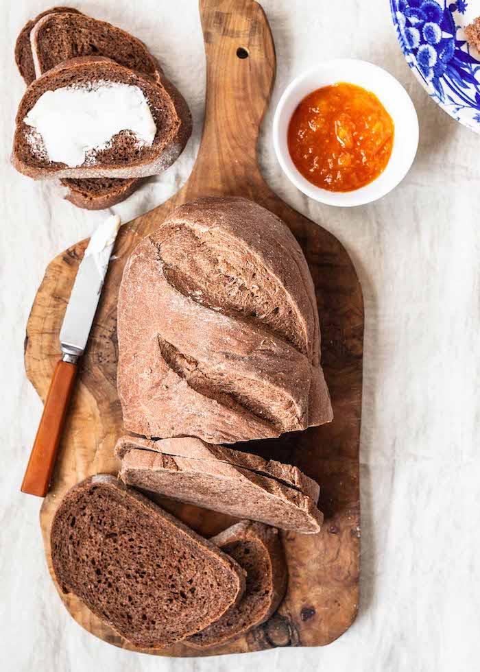 pain complet avec de la farine complète à déguster avec beurre et confiture, pain sur planche à découper