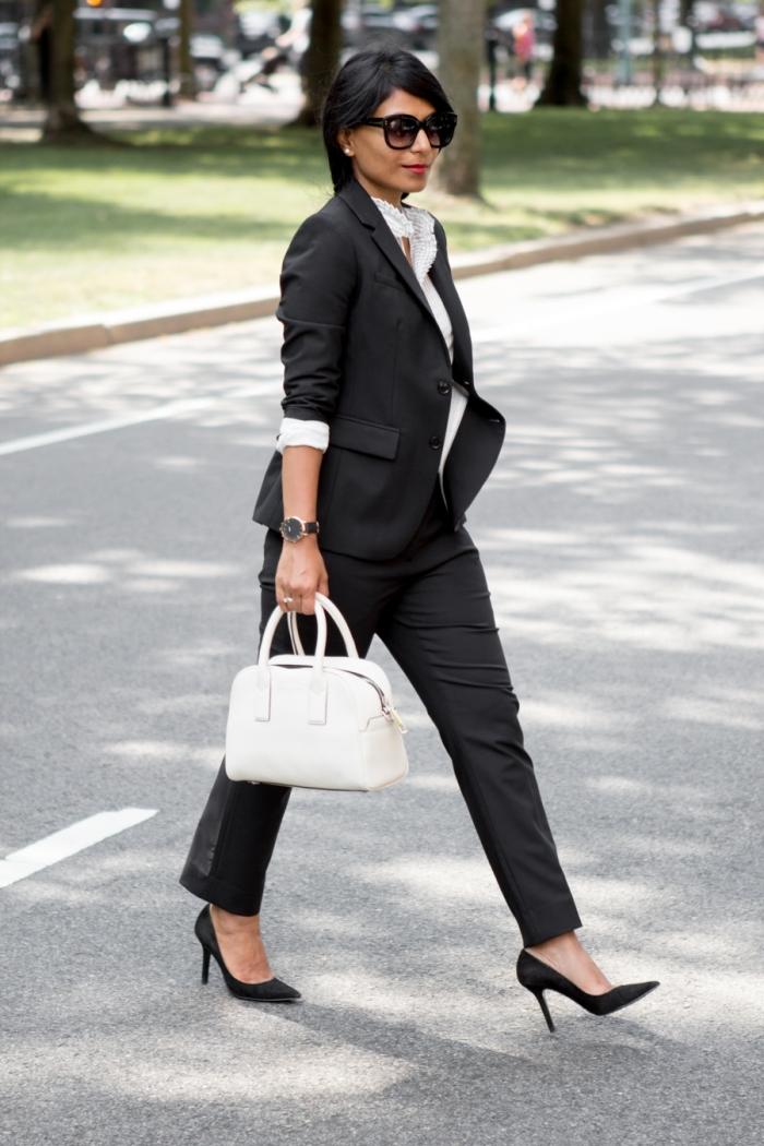 idée de tenue stylée avec ensemble tailleur femme de couleur noire en combinaison avec une chemise et sac à main blancs