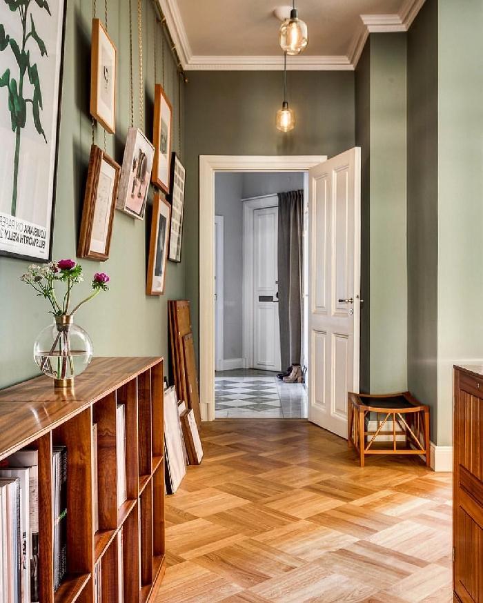 peinture couloir vert porte blanche parquet bois meubles de rangement ouvert en bois vase verre ronde mur de cadres bois rustique