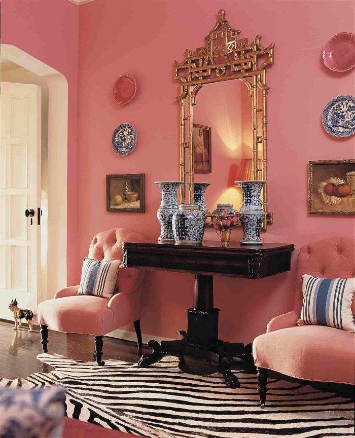 peinture murale rose aménagement entrée maison fauteuil tissu boutonné rose meuble bois foncé cadre miroir or tapis imitation zèbre