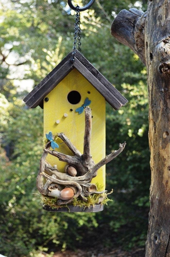 modèle de petite mangeoire aux murs jaunes avec toit noir et décoration en branches de bois, fabriquer un nichoir pour mésange