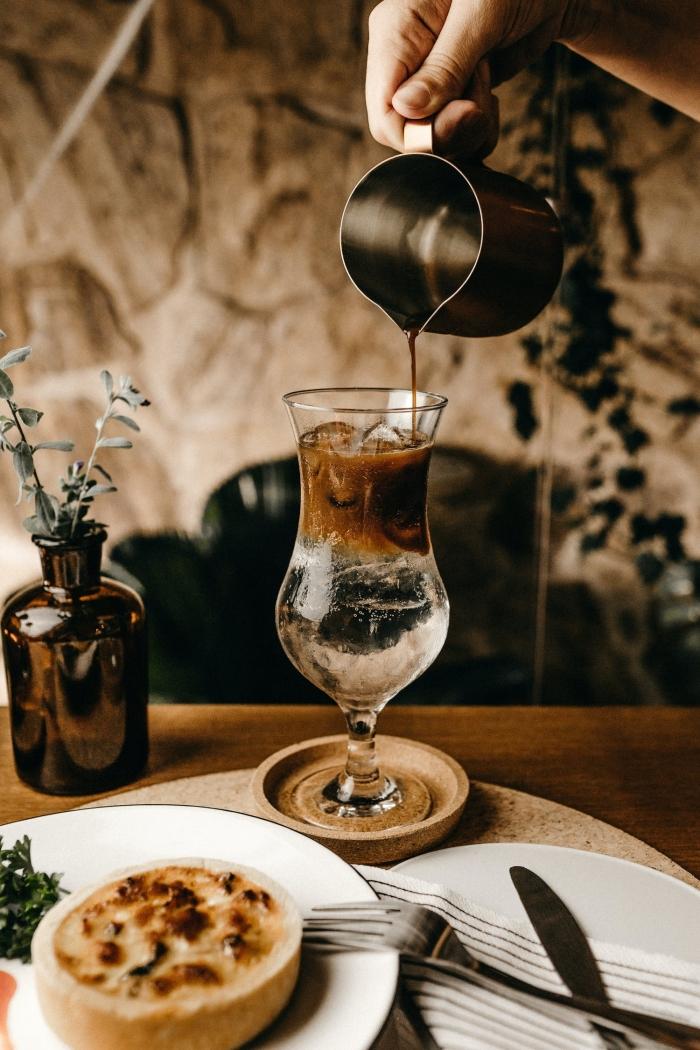 idée comment faire un café glacé nespresso facile, servir un café froid dans un verre à cocktail originale sur un sous-verre bois