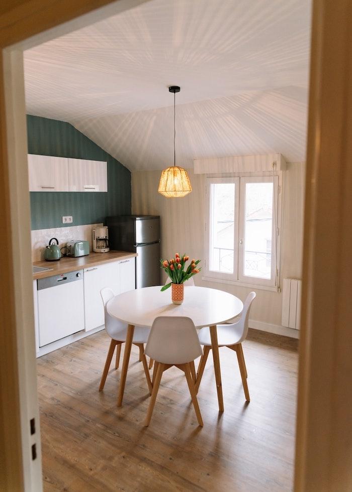 Table à manger ronde, chaises blanches, mur vert tendance cuisine 2020, peinture salle a manger qui donne à la cuisine