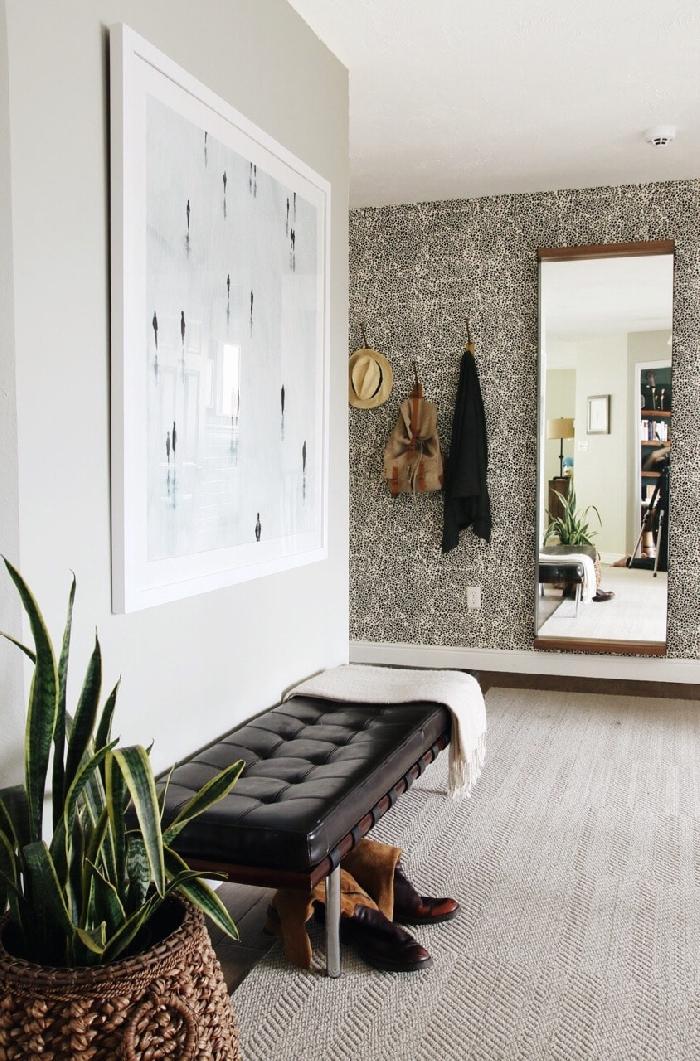 plante verte d intérieur cache pot tressé fibre végétale banquette entrée cuir noir tapis blanc peinture gris clair miroir rectangulaire