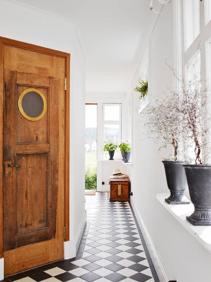 porte d entrée bois rustique déco couloir étroit carreaux sol blanc et noir coffre bois foncé pot de fleur béton vase murs blancs