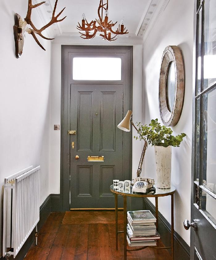 porte grise poignée or miroir pierre aménager une entrée de style rustique cornes décoratives parquet bois foncé table ronde or