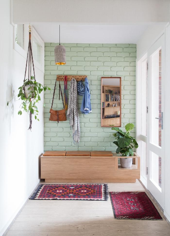 quelle couleur pour agrandir un couloir mur briques vert pastel crochet rangement banquette bois siège cuir marron plante suspendue