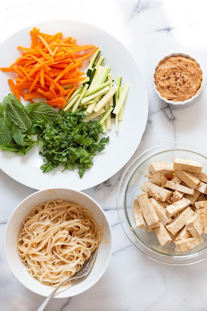 crudités, nouilles et tofu mariné pour faire un rouleau de printemps vegan, idée originale de repas à partager entre amis