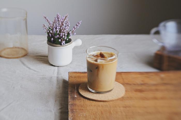 recette café glacé facile à réaliser soi-même, verre de café froid au lait et glaçons sur une plateau en bois et sous verre