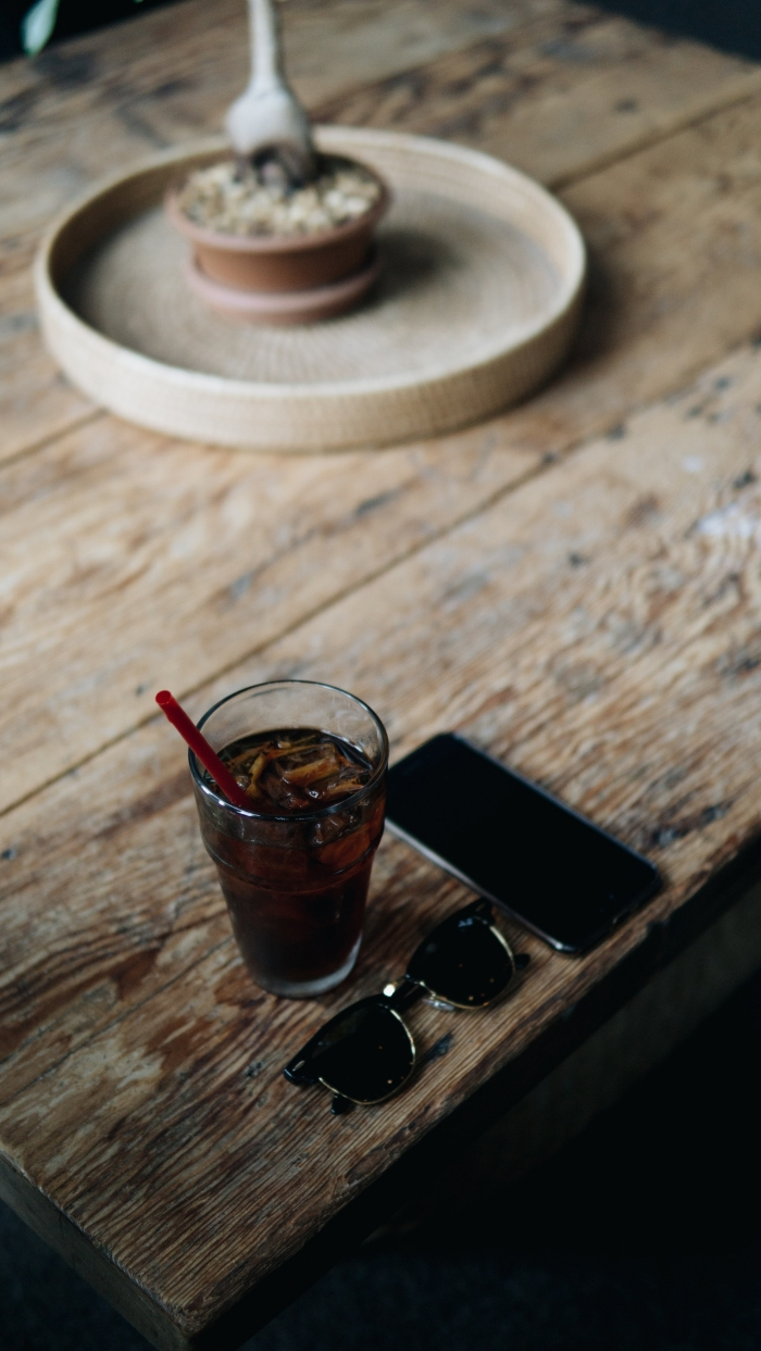 idée comment préparer une chicorée boisson originale, verre rempli de café noir avec glaçons sur une table bois brut
