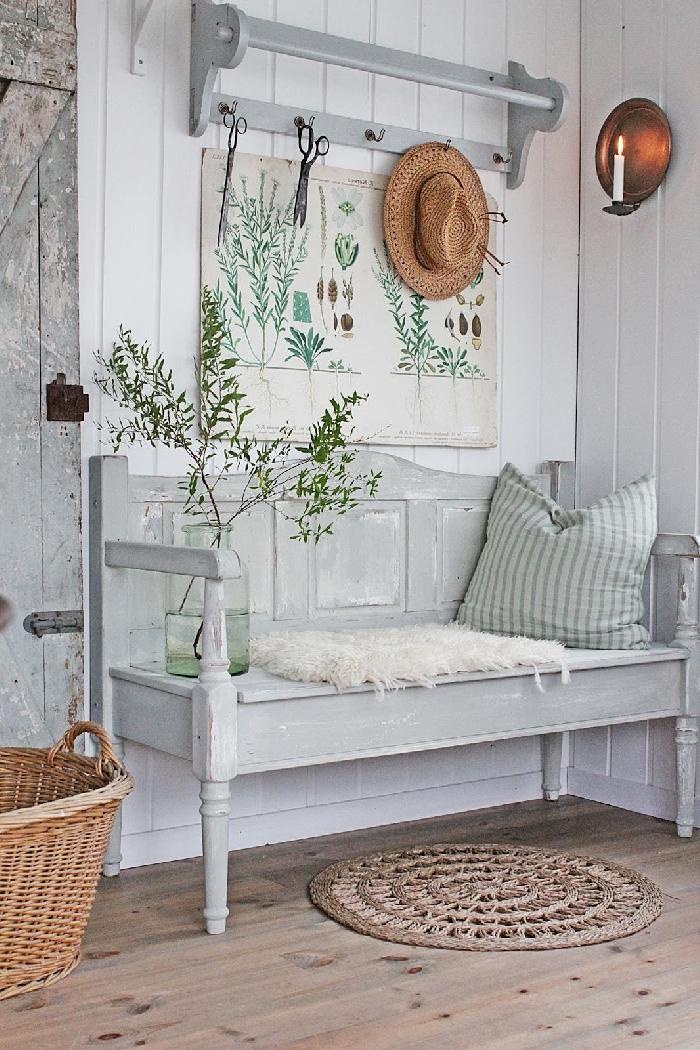 revêtement mural panneaux blancs banquette entrée style vintage panier tressé fibre végétale coussin décoratif vase verre housse fausse fourrure blanche