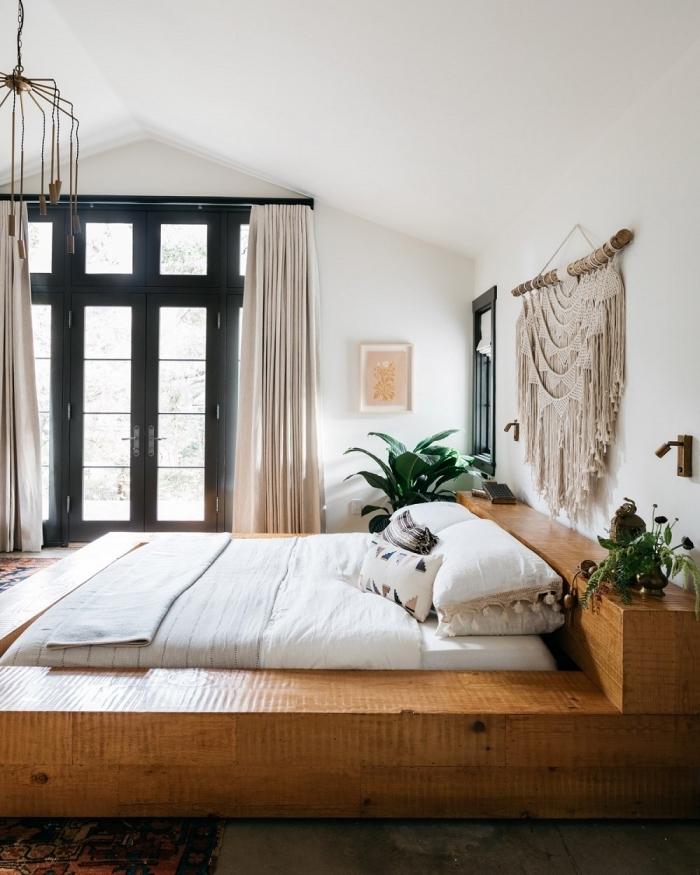 rideaux longs beige cadre de lit bois plantes vertes d intérieur coussins décoratifs motifs géométriques oreillers pompons suspension en macramé