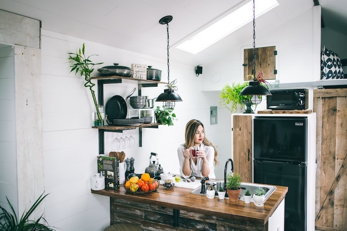 Femme qui boit son café dans la cuisine rustique en blanc et bois, couleur de peinture pour cuisine, tendance couleur cuisine 2020
