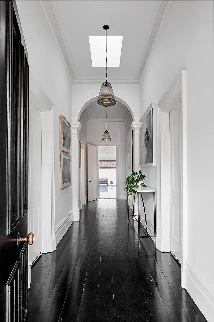 sol parquet noir comment peindre un couloir aux multiples portes décoration blanc et noir porte noire plante verte cadre photo bois