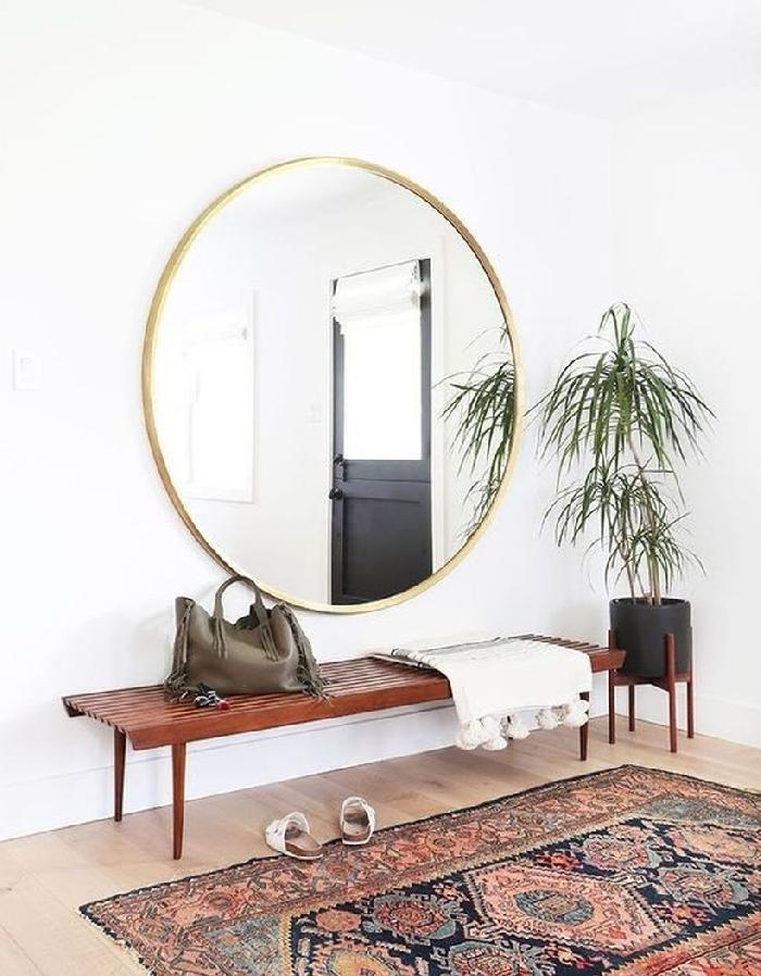 style bohème moderne palmier d intérieur banquette bois foncé décoration de couloir d entrée large miroir cadre or tapis marron