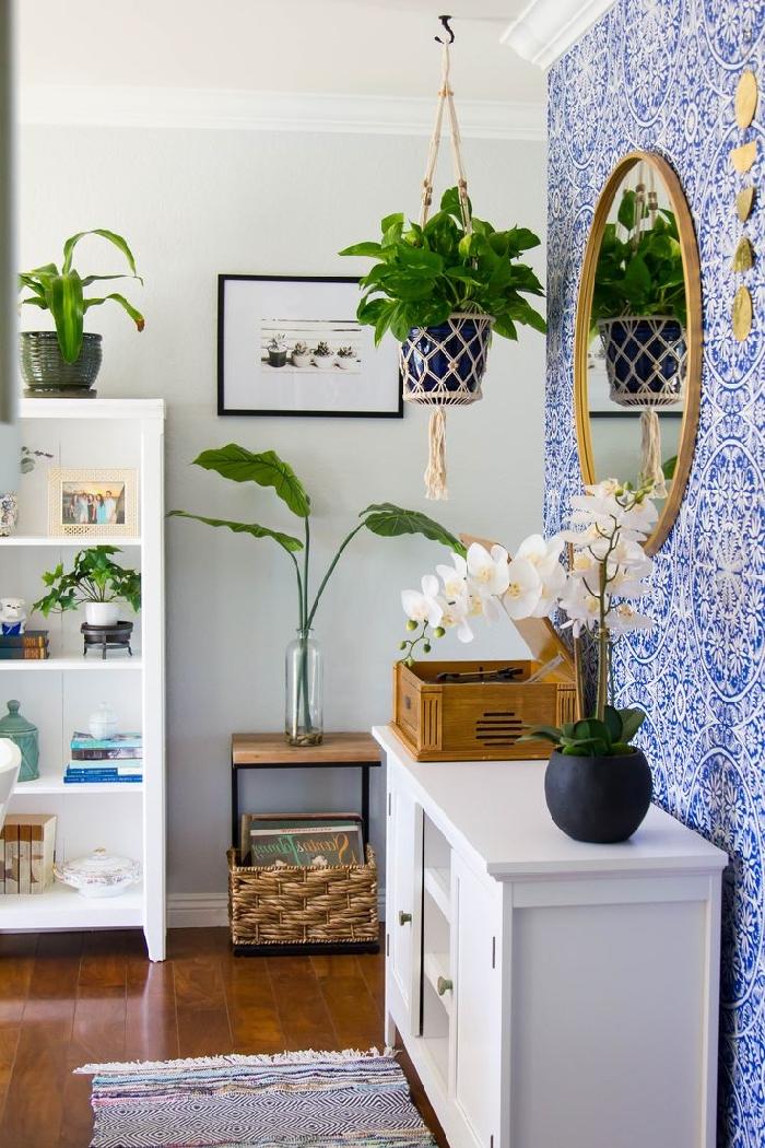 suspension plante macramé papier peint bleu et blanc meubles bois blanc tapis multicolore franges cadre photo noir peinture couloir