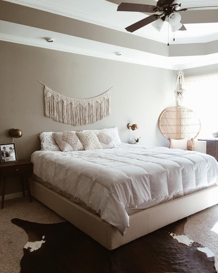têtе de lit en macramé ventilateur de plafond peinture murale grise chaise paon rotin tapis imitation peau animale lampe de chevet dorée