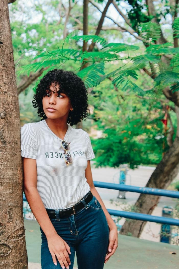 t shirt blanc jeans taille haute foncé ceinture cuir noir coupe afro femme maquillage rouge à lèvre doré fards à paupières