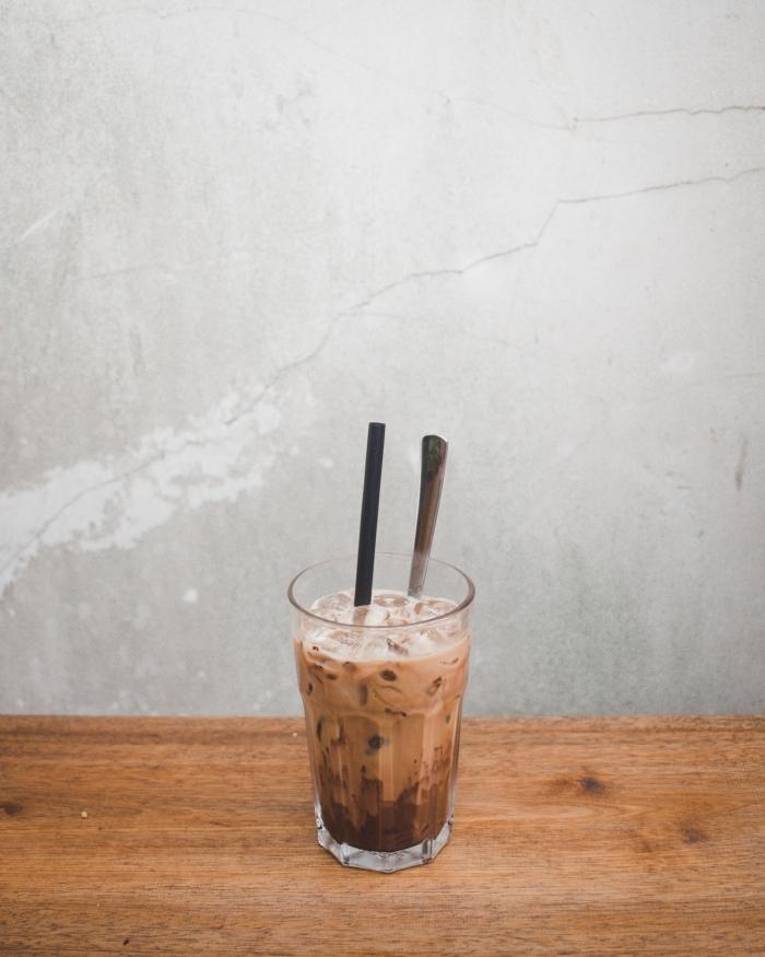 comment faire un latte glacé facile, exemple de verre rempli de café au lait refroidi avec glaçons et chocolat fondu