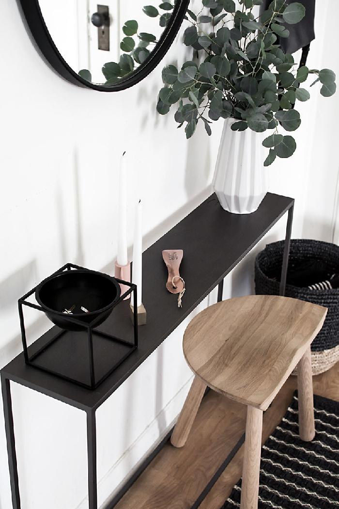 tabouret bois panier tressé beige et noir décoration entrée appartement cadre miroir noir vase origami blanc plante verte accessoires