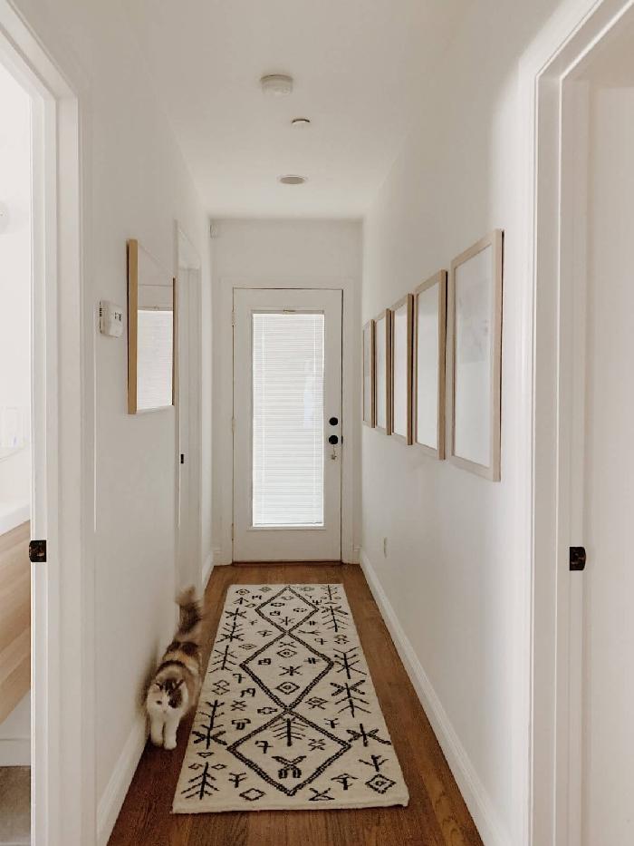 tapis blanc et noir motifs aménager une entrée étroite de style minimaliste cocooning cozy intérieur couloir mur de cadres bois