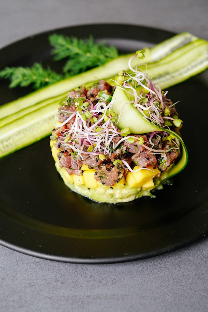 tartare thon avocat avec couche d avocat, ouche de mangue et couche de thon surmontée de graines germées et concombre