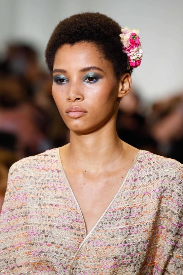 tendance coiffure cheveux crépus accessoire cheveux fleurs rose et blanc coupe courte femme afro robe beige oversize décolleté en v