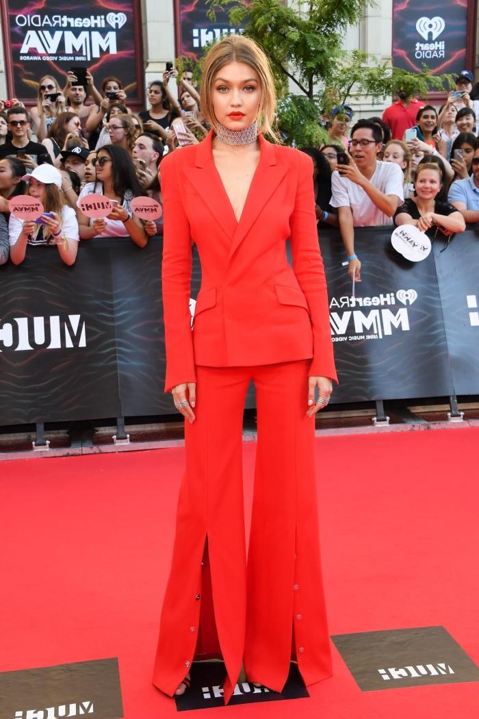 look de soirée avec costume femme de couleur rouge, Gigi Hadid habillée en tailleur pantalon femme pour cérémonie