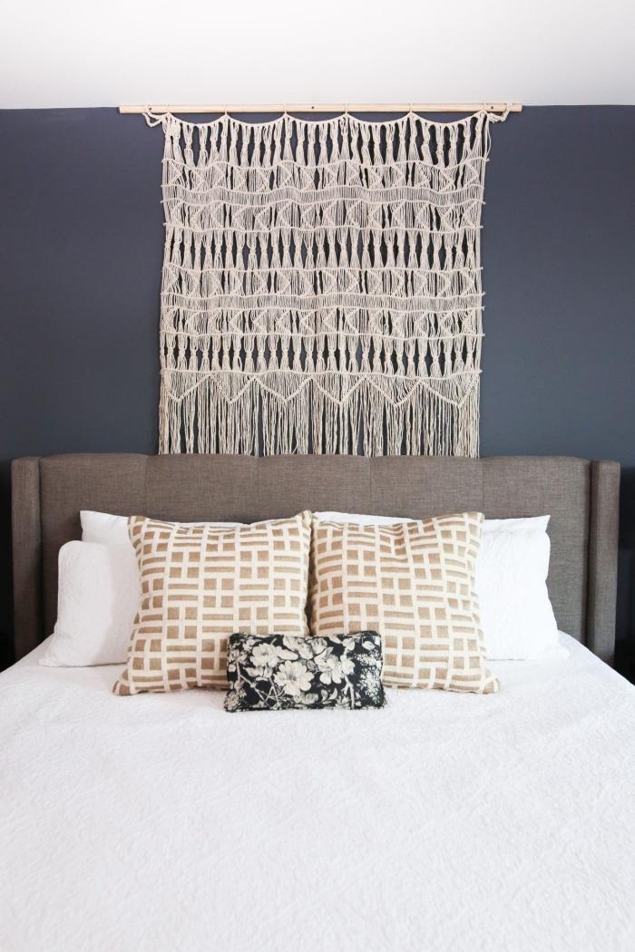 tete de lit diy en corde macramé beige bâton bois peinture murale bleu foncé tête de lit gris coussin décoratif motifs floraux blanc et noir