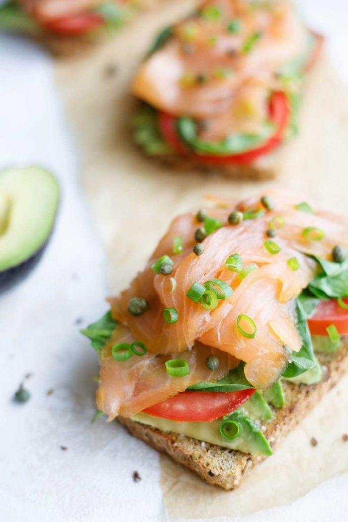 idée d entrée froide, exemple de toast avocat avec des tranches d avocat rangées sur pain, tomate et saumon fumé