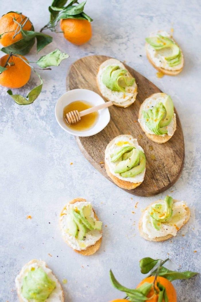 toast apéritif, recette avocado toast à base de fromage ricotta et des tranches d avocat dessus avec miel
