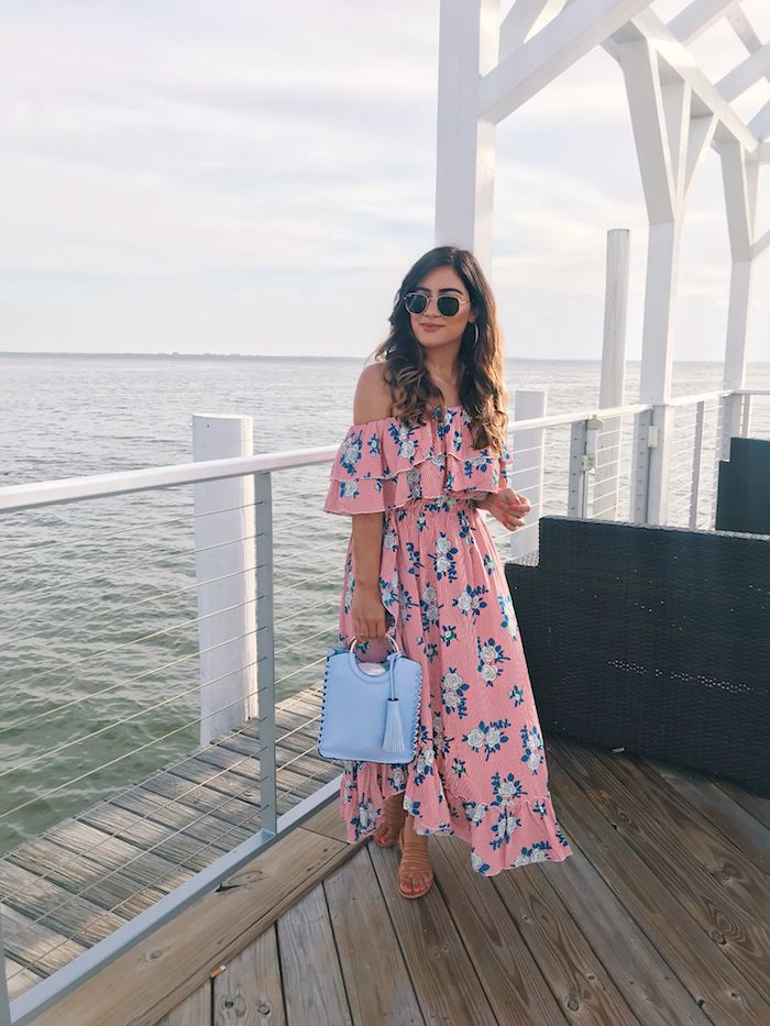 vacances au bord de la mer belle robe longue rose sac a main bleu claire et robe fleurie femme robe d été fleurie pour femme romantique fille cheveux bouclés lunettes de soleil ray ban