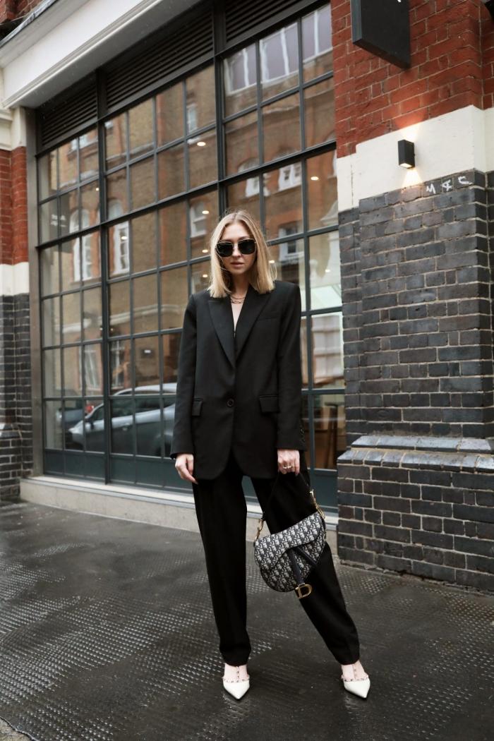 idée de tenue femme stylée en costume oversize de couleur noir assortie avec paire de chaussures blanches, modèle de pantalon tailleur femme