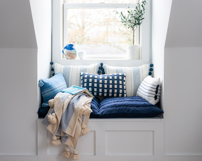 amenagement niche murale combles perdus avec banc encastré coin lecture avec coussins bleu et blanc plante verte et petite fenetre
