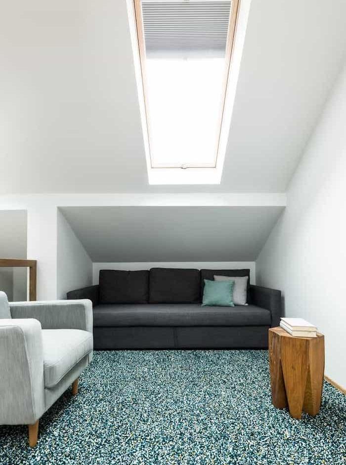 amenagement sous pente de coin lecture bas avec canapé gris anthracite table en rondin de bois et fauteuil gris clair