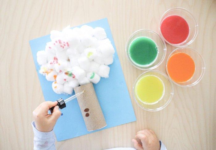 arbre en coton et rouleau de papier toilette sur papier bleu peinture maternelle avec de la peinture de couleurs variée dessin original enfant