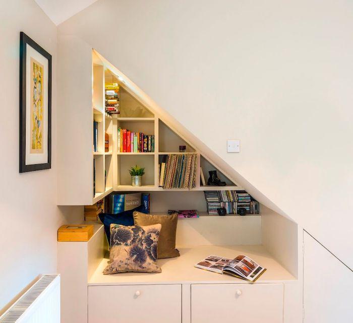 banc de lecture sous pent mur aux étagères blanches avec des livres coussins colorés idee deco cosy