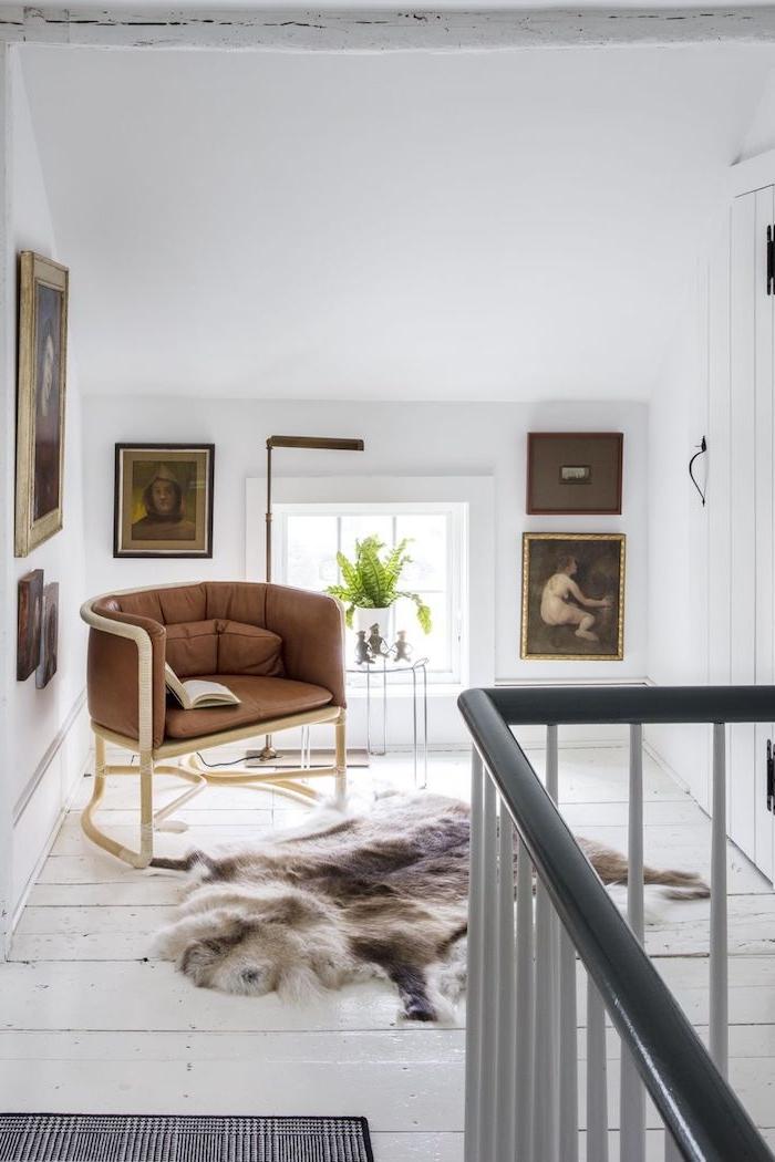 bibliotheque mezzanine avec fauteuil lecture confortable mur de cadres d art petite table de service decorative tapis fourrure