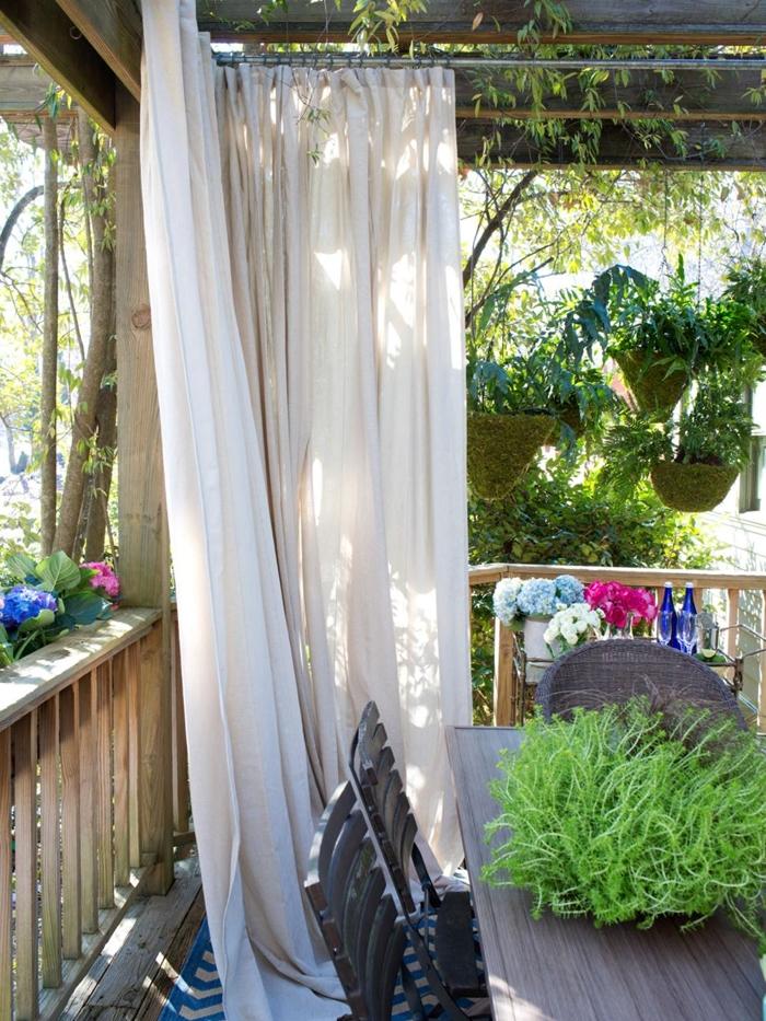 brise vue vegetal rideau blanc décoration véranda maison terrasse en bois pots de fleurs suspendus meuble extérieur bois foncé