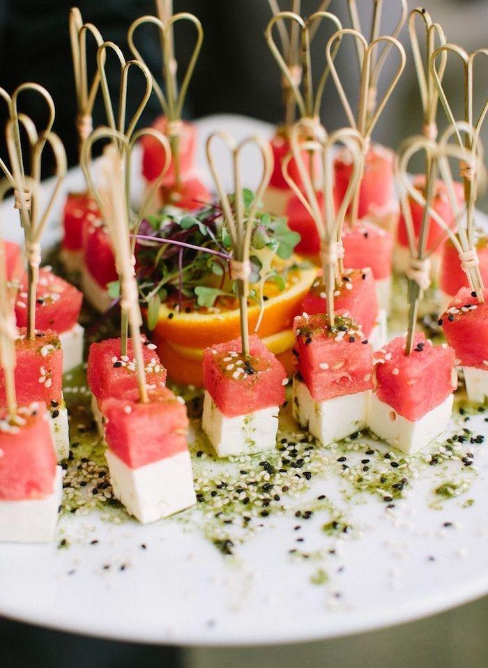 brochettes apéritives de cubes de pasteque et fromage feta aux graines de sesame avec des rondelles d orange au centre