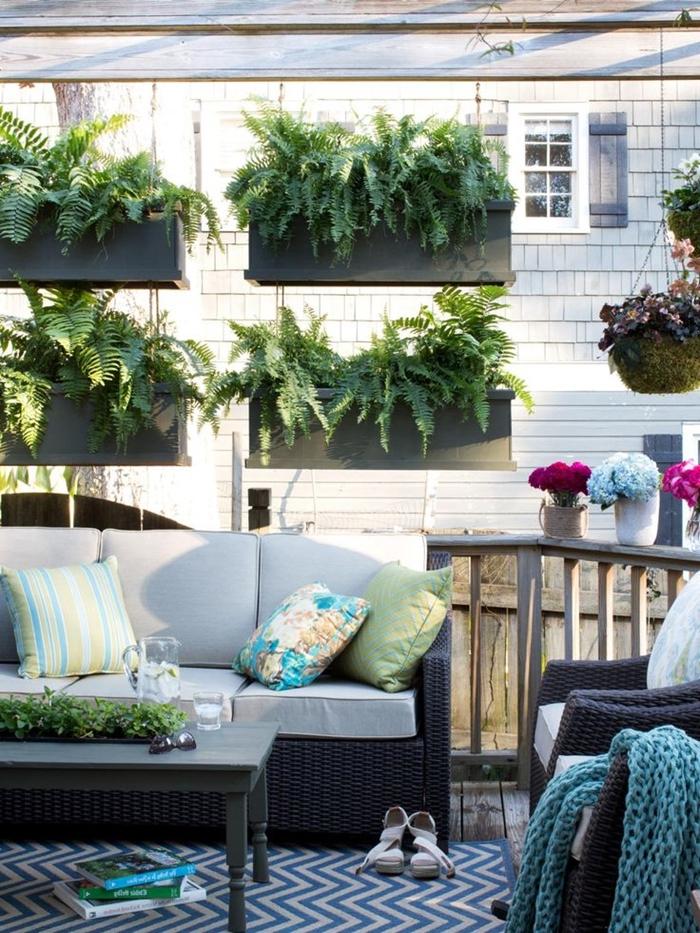 cache balcon décoration extérieure idée cache vue appartement avec plantes suspendues jardinières plantes vertes coussins décoratifs
