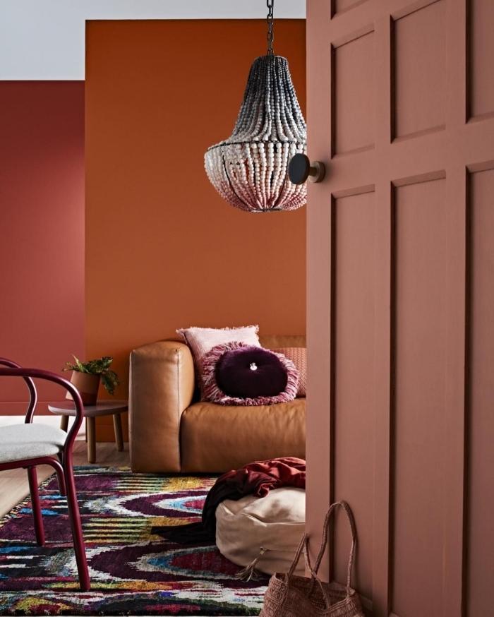 canapé cuir camel design salon bohème chic accessoire ethnique tapis multicolore coussin décoratif peinture terracotta lustre coquillage