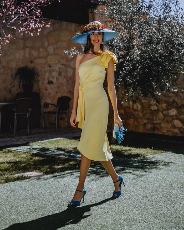 capeline bleu ornements fleurs pochette bleue franges robe de ceremonie élégante couleur jaune pastel col asymétrique épaule dénudée sandales bleues