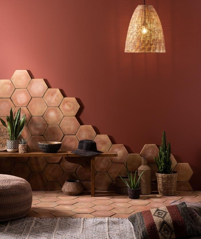 carrelage beige motifs hexagonaux lampe suspendue tressée peinture terracotta décoration bohème banquette bois pouf crochet plantes