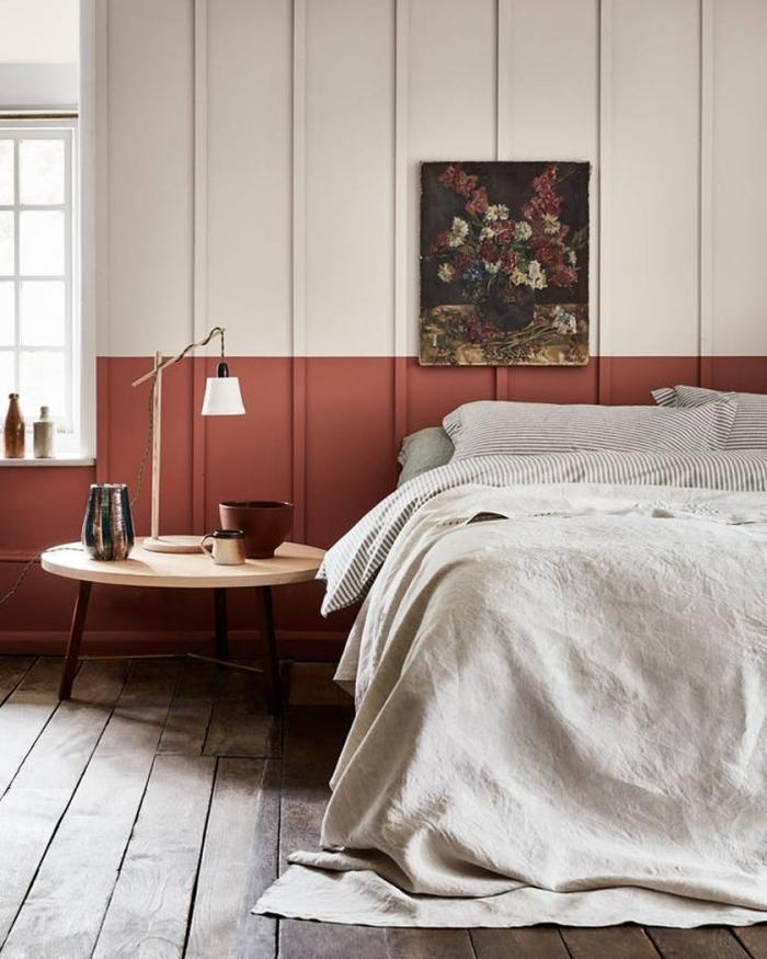 chambre terracotta mur bicolore peinture fleurs lampe de chevet blanc et bois table basse ronde en bois clair poterie terre cuite vase doré