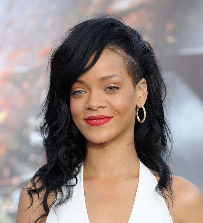 coupe asymétrique femme avec côté légèrement rasé et des cheveux noirs ondulés longs avec volume sur le dessus