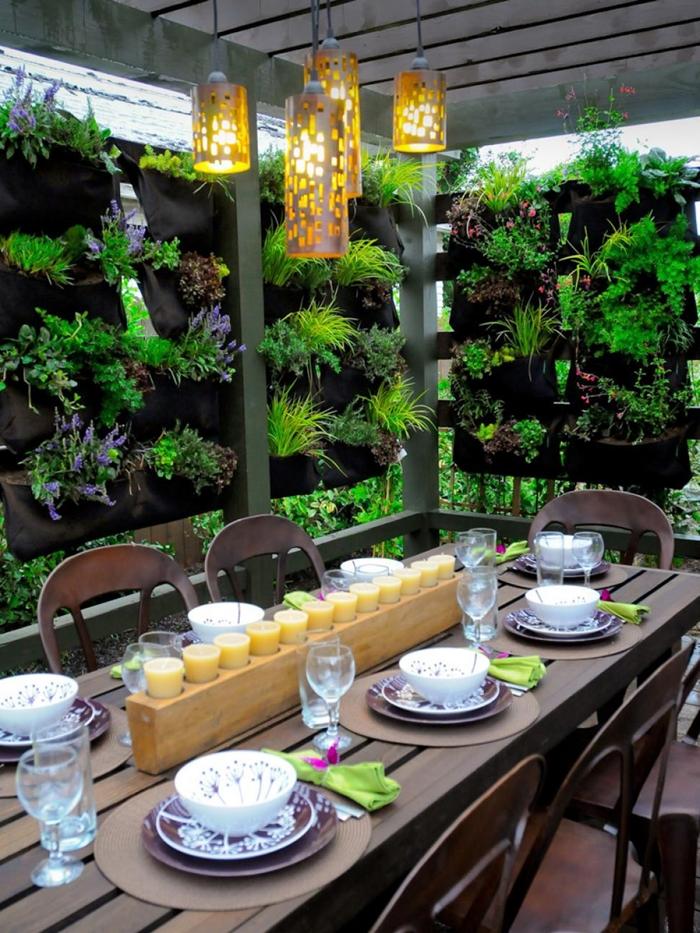 décoration cour arrière pergola meubles extérieur bois foncé table brise vue vegetal éclairage extérieur bougies centre table
